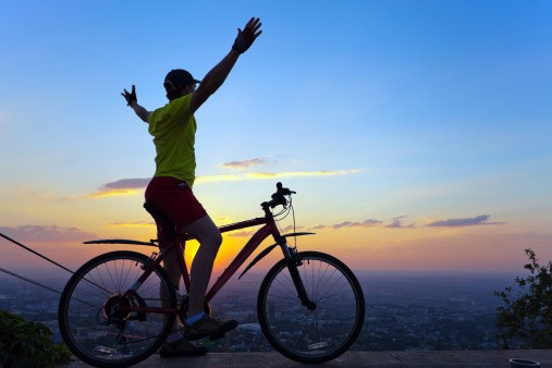 Young man with a bicycle at sunset.